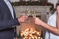 Couple celebrating New Year. Merry Christmas and Happy New Year! Cropped image of elegant couple clinking glasses of champagne together while celebrating Royalty Free Stock Images