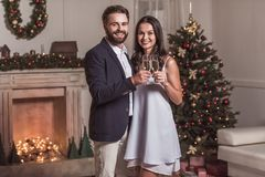 Couple celebrating New Year. Merry Christmas and Happy New Year! Cheerful and elegant couple is holding glasses of champagne, looking at camera and smiling while Stock Photography