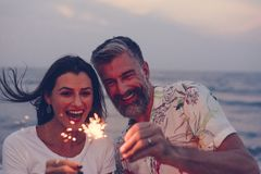 Couple celebrating with sparklers at the beach stock photos
