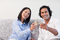 Couple celebrating with sparkling wine on the couch Stock Image