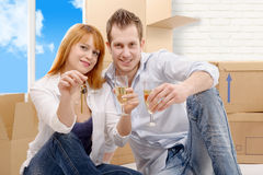 Couple celebrating their new home, keys  and champagne in hand. Stock Photo