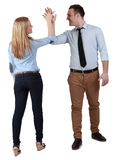 Couple celebrating their success. Happy young couple celebrating their success giving each other a high five, against a white background Royalty Free Stock Images