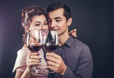 Couple celebrating Valentines day drinking red wine. On black background Stock Image