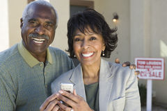 Couple With Cell Phone In Front Of New House stock photography