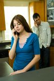 Couple on Cell Phones. Man and woman talking on cell phones in the kitchen of home Royalty Free Stock Photography