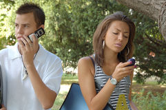 Couple with cell phones. Man and woman using cell phones outside Stock Images