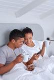 Couple cellphone bed Stock Images