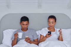 Couple cellphone bed Stock Photography