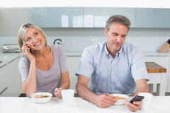 Couple with cellphones while having breakfast Stock Images