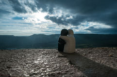 Couple of ceramic figures hugging on background mountain sunset, silhouette two romantic people cuddling and looking on rear view Stock Images