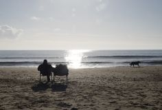 Couple in chairs on beach with dog walking. A silhouetted couple sitting in chairs on Bournemouth beach in January with the sun reflecting in the sea and a dog Stock Images