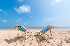 Couple of chairs on sandy beach on sunny day looking for the blu Stock Images