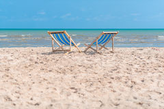 Couple of chairs on sandy beach on sunny day looking for the blu Royalty Free Stock Images