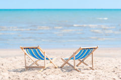 Couple of chairs on sandy beach on sunny day looking for the blu Royalty Free Stock Image