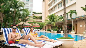 Couple on chaise-longues. Couple in sunglasses sitting on chaise-longues near hotel pool stock photos