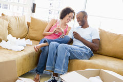 Couple with champagne by boxes in new home Stock Photography