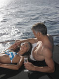 Couple With Champagne Flute Relaxing On Yacht Stock Photography