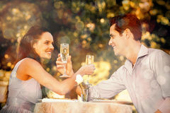 Couple with champagne flutes sitting at outdoor café. Smiling young couple with champagne flutes sitting at an outdoor caf Stock Photo