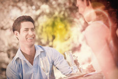 Couple with champagne flutes sitting at an outdoor café Royalty Free Stock Photos
