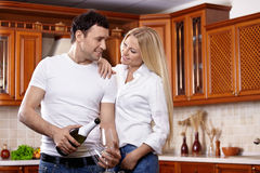 Couple with champagne on kitchen Royalty Free Stock Photography