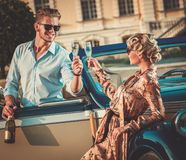 Couple with champagne near classic car Royalty Free Stock Photography