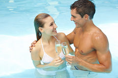 Couple with champagne in pool Royalty Free Stock Photo