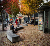 Couple chats on concrete bench, autumn in Portugal. Leaves changing and falling in Porto, city scene with couple sitting on a park bench in front of newsstand Stock Image