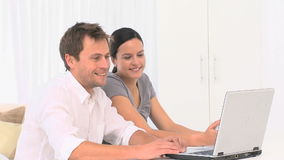 Couple chatting on internet with a laptop stock footage