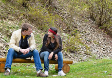 Couple chatting outdoors sitting on Royalty Free Stock Image