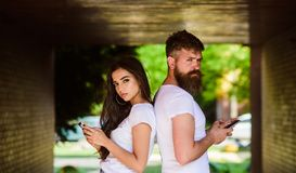 Couple chatting smartphones. Girl attractive brunette bearded hipster man stand back to back porch underground crossing. Couple chatting smartphones. Girl royalty free stock photo