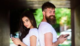 Couple chatting smartphones. Girl and bearded man stand back to back porch or underground. Couple ignore real. Couple chatting smartphones. Girl and bearded men stock image