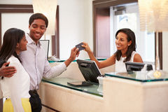 Couple Checking In At Hotel Reception Royalty Free Stock Photos