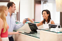 Couple Checking In At Hotel Reception Royalty Free Stock Photo