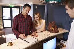 Couple Checking In At Hotel Reception Desk Stock Image