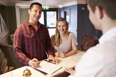 Couple Checking In At Hotel Reception Desk Royalty Free Stock Images