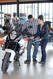 Couple checking motorbike at local salon Stock Photography