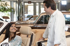 Couple checking out new cars in dealership showroom Stock Images