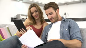 Couple Checking Personal Finances Using Digital Tablet. Young couple at home looking at bills and checking personal finances together using digital tablet.Shot stock footage
