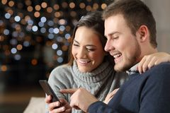 Couple checking phone content in winter at home. Couple checking phone content in winter sitting on a couch in the living room at home royalty free stock photography