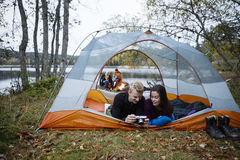 Couple Checking Photos Into Camera While Lying In Tent Stock Photos