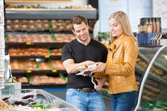 Couple Checking Product Ingredients At Butcher's Royalty Free Stock Photo