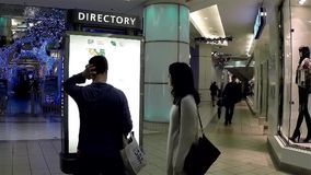 Couple checking store position in front of  directory sign inside shopping mall stock video footage