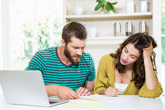 Couple checking their bills in kitchen. At home Stock Photo