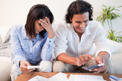 Couple checking their bills in the living room Stock Photography