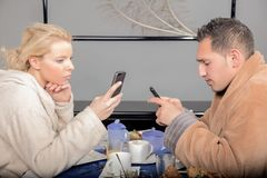 Couple checking their mobile phones at breakfast Royalty Free Stock Photos