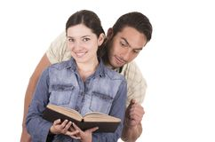 Couple of cheerful happy attractive students. Holding book reading together isolated on white Stock Photos