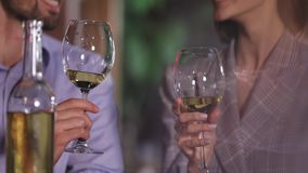 Couple cheering with white wine glasses on romantic dinner. At restaurant closeup stock video footage