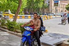 Couple with child rides down street on motorcycle, Isfahan, Iran. Isfahan, Iran - April 24, 2017: A family of three Iranians is riding motorbike stock images