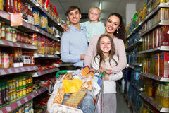 Couple with children buying food in hypermarket Royalty Free Stock Images