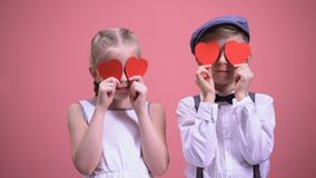 Couple children closing eyes with paper hearts, enjoying happy Valentines day stock video footage